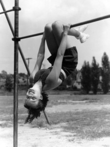 h-armstrong-roberts-smiling-teen-girl-on-playground-hanging-upside-down-on-monkey-bars